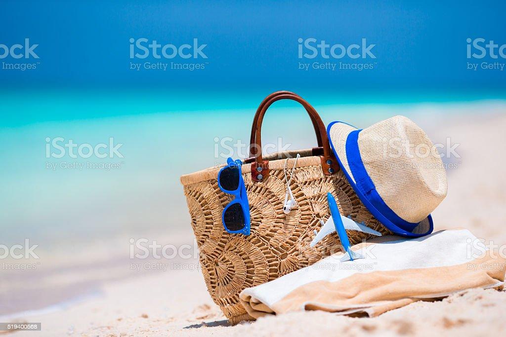 Beach accessories - bag, straw hat, sunglasses on white beach stock photo