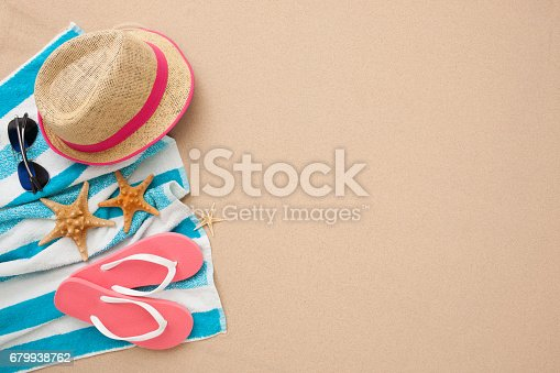 Beach accessories: pink flipflop, straw hat, towel and sunglasses isolated on sand.