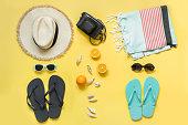 2つのビーチアクセサリー、ストロービーチ帽子、タオル、イエローのサングラス。夏のコンセプトとトロピカルな休暇。