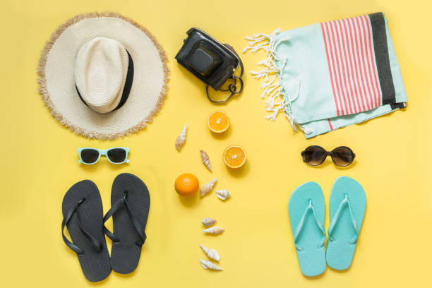 Beach accessories for two, straw beach sunhat,towel, sun glasses on yellow. Summer concept and tropical vacations. Beach accessories for two, straw beach sunhat,towel, sun glasses on yellow with space for text. Summer concept. knolling concept stock pictures, royalty-free photos & images
