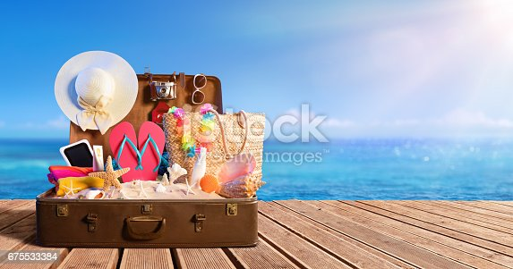 istock Beach Accessories In Suitcase On Beach - Travel Concept 675533384