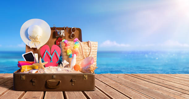 beach accessories in suitcase on beach - travel concept - vacanze foto e immagini stock