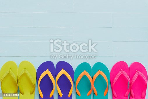 955947208 istock photo Beach accessories including colorful flip flop on bright blue pastel wooden background for summer holiday and vacation concept. 966369380