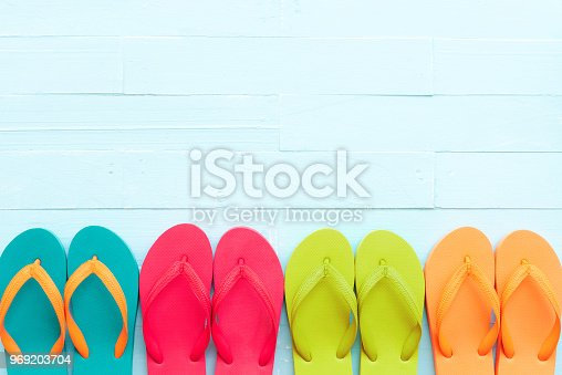 955947208 istock photo Beach accessories including colorful flip flop on bright blue pastel wooden background for summer holiday and vacation concept. 969203704
