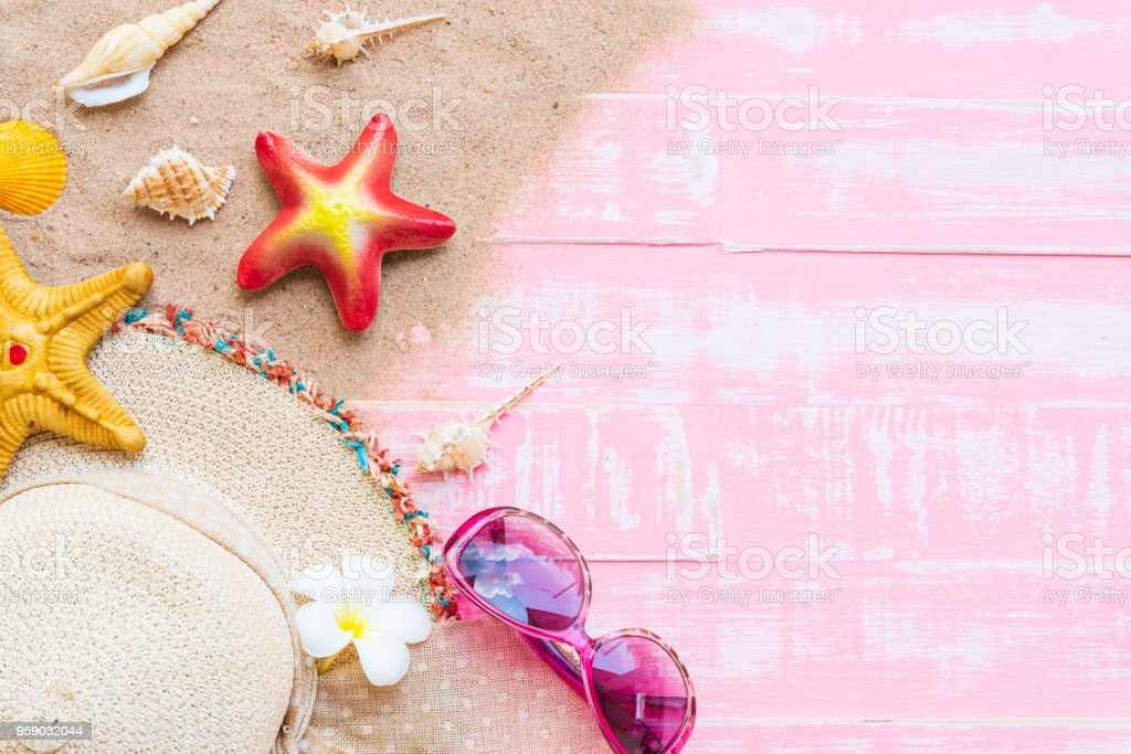 Beach accessories including sunglasses, starfish, hat beach and shell on bright pink pastel wooden background for summer holiday and vacation concept. stock photo