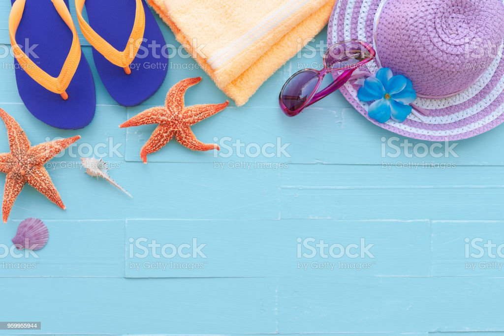 Beach accessories including sunglasses, starfish, hat beach,yellow towel,colorful flip flop and shell on bright blue pastel wooden background for summer holiday and vacation concept. stock photo
