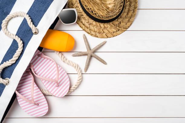 strand-accessoires auf weißer holztisch. - salzwasser sandalen stock-fotos und bilder