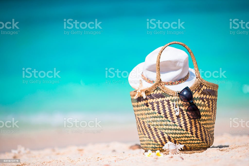 Beach accessories - straw bag, sunglasses, hat on the beach stock photo
