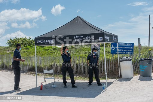 June 13, 2020 - Miami Beach, Florida USA - Beach ambassadors remind beachgoers of the new rules: to have a face mask ready at all times and to socially distance during the coronavirus pandemic.
