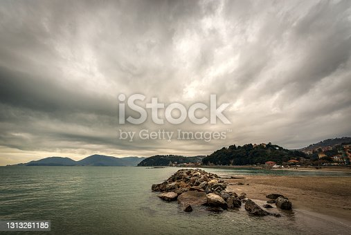 Beach and sea of the town of Lerici in winter, tourist resort in the Gulf of La Spezia, Liguria, Italy, Europe. On the horizon the San Terenzo village and the Porto Venere or Portovenere town.