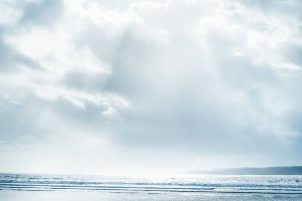 Beach and sea with cloudy sky and sunbeams. stock photo