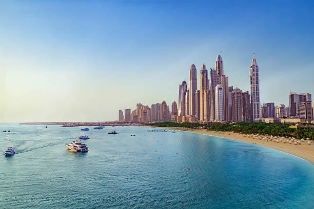 beach and skyline of dubai marina - dubai stock-fotos und bilder