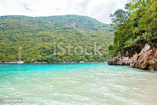Secret Beach and tropical resort, Labadee island, Haiti. Exotic wild beach with palm and coconut trees against blue sky and azure water