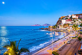 Stock photograph of beach and waterfront promenade in Mazatlan, Sinaloa, Mexico at twilight blue hour.