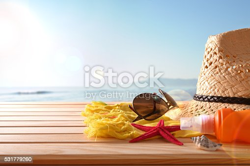 istock Beach articles on a table wooden slats and sea background 531779260