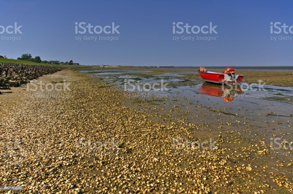 Beach at low tide with small pebbles, mudflats and bright red fishing boat stock photo