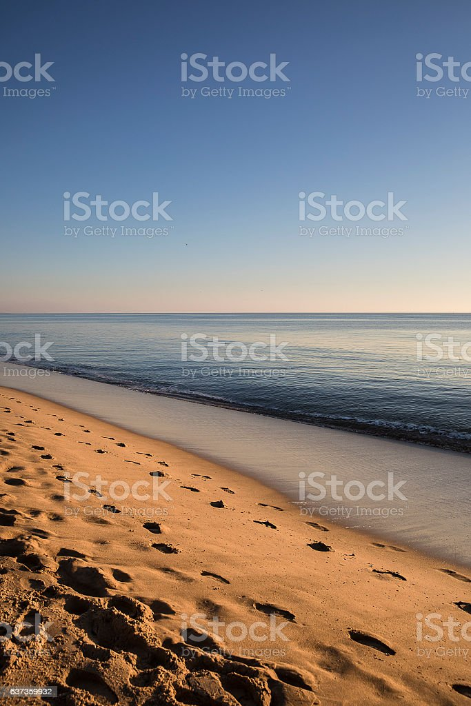 beach at sunset with golden sand and quiet sea stock photo