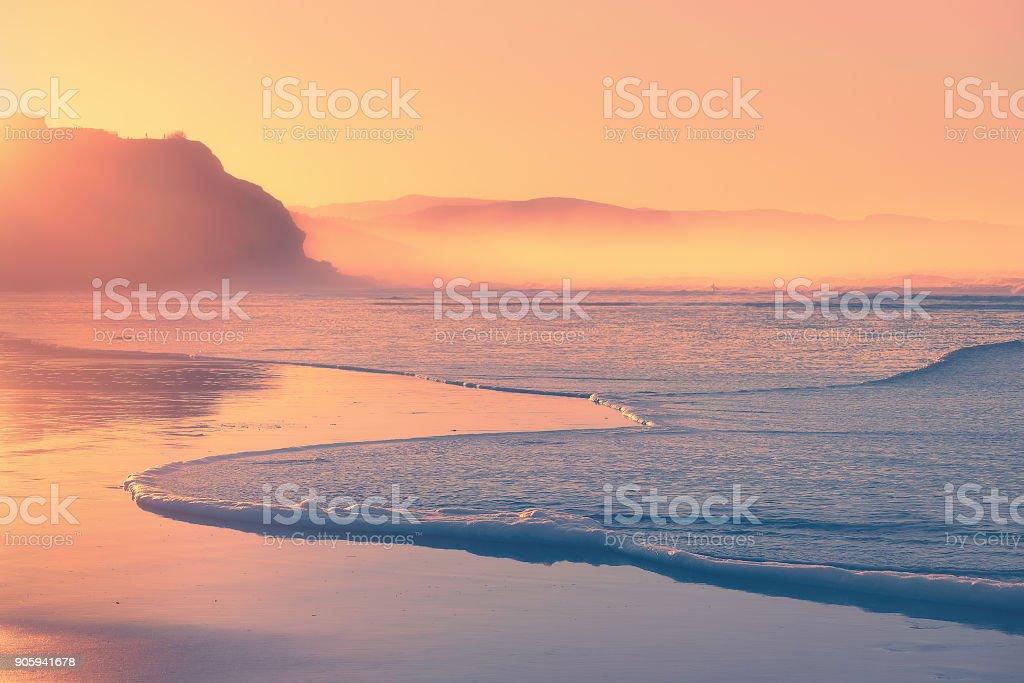 Playa al atardecer con espuma de la ola en la costa - foto de stock