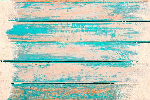 Beach background - top view of beach sand on old wood plank in blue sea paint background. summer vacation concept. vintage color tone.