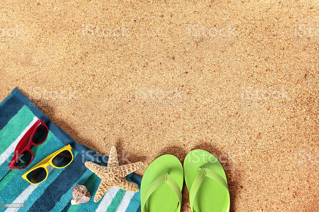 Beach background scene with sunglasses and flip flops stock photo
