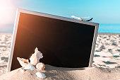 istock Beach background. Starfish, seashells, toy plane and globe near blackboard on ocean nature beach. Design of summer vacation holiday concept. 1311857733