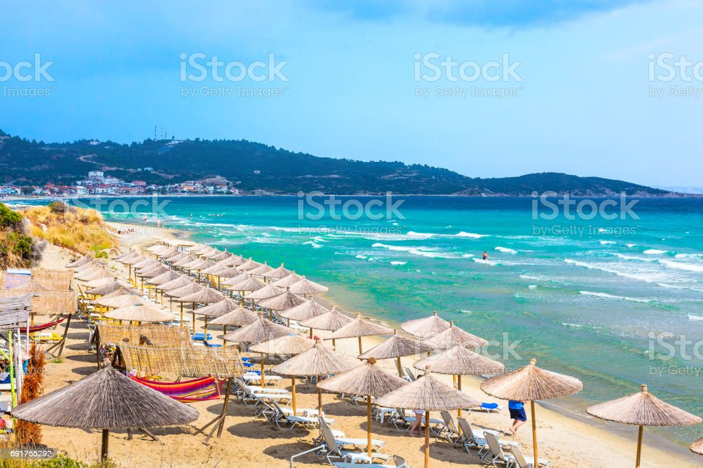 beach background with turquoise sea water waves and umbrellas, Greece stock photo