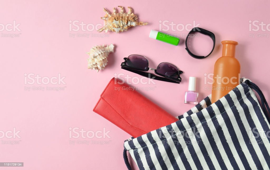 Beach bag and accessories for relaxing on the beach layout on pink...