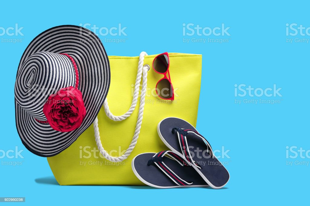 Beach bag, hat and other beach stuff  on blue background. stock photo