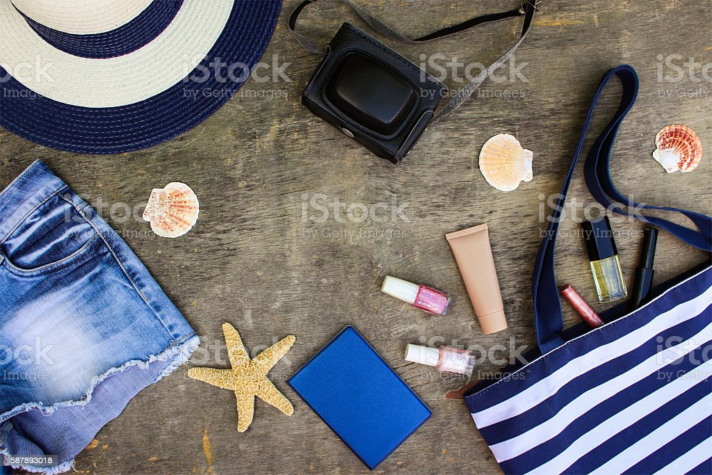 Beach bag, sun hat, cosmetics, denim shorts, camera, seashells - foto de stock