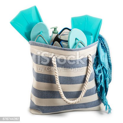 Nicely isolated on a pure white background, the beach bag contains several items, such as fins, sandals, goggle and sarong. In a duotone mode based on blue and white tones, studio shot and professionally isolated.
