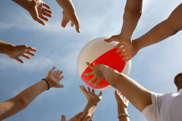 beach ball being boundced around by hands in the sun - beach ball stock photos and pictures