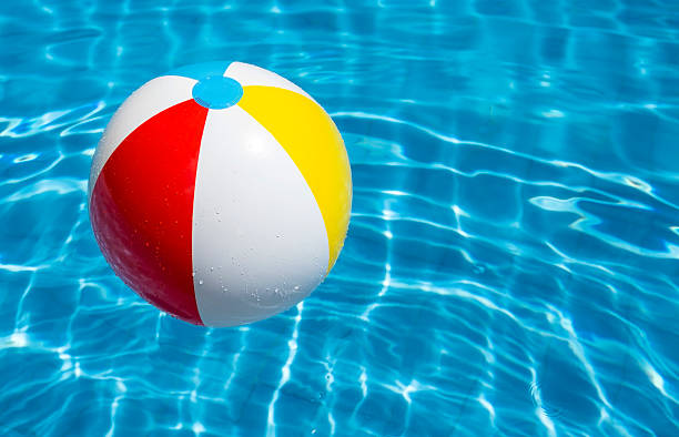 a beach ball floating in a blue pool - beach ball stock photos and pictures