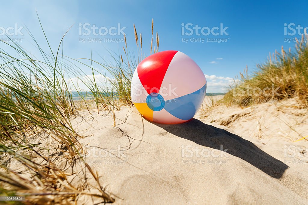 Beach ball resting in sand dune concept for childhood summer...