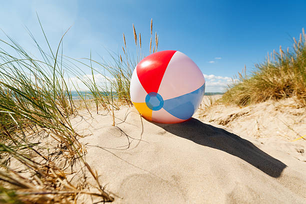 beach ball in sand dune - beach ball stock photos and pictures