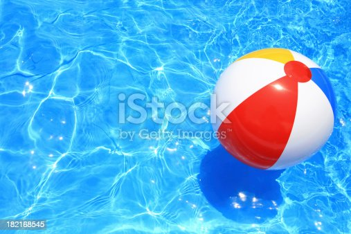 Beach ball floating in a pool with small waves reflecting in the summer sun.