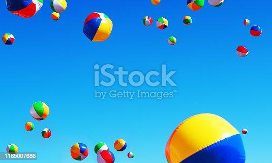 Many beach balls bounce into the Summer sky.