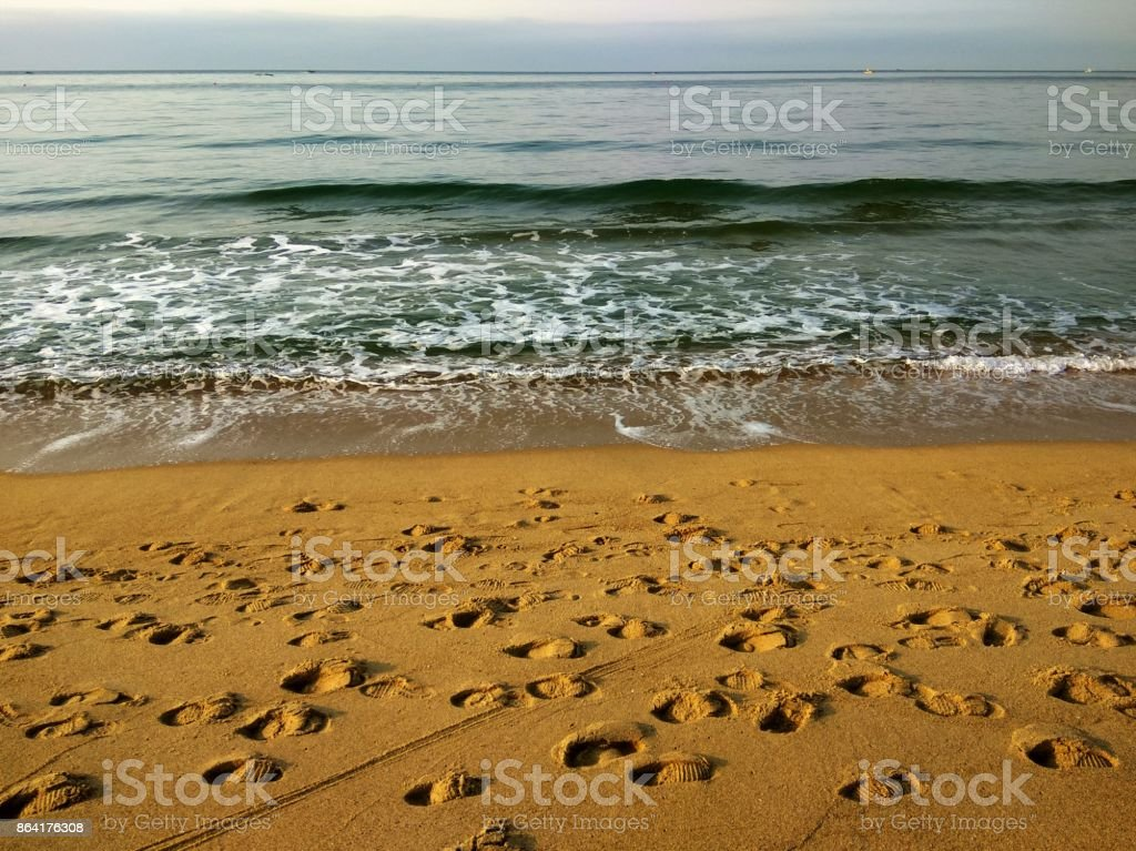 Beach beautiful seashore waves and footprints royalty-free stock photo