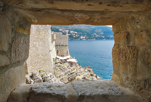Beach behind the wall of Dubrovnik framed in a window