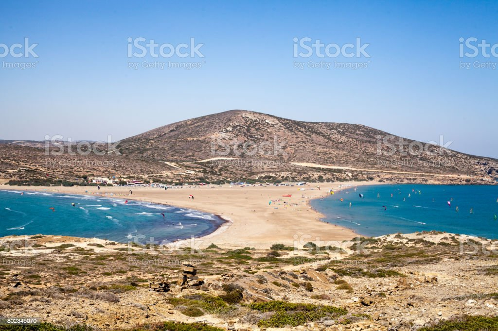 Beach between two seas. Beach between the islands of Rhodes and Prasonisi. Road across the sea. People practicing Kitesurfing. Colorful kites on the sea shore. Blue waves sea and sky. – zdjęcie