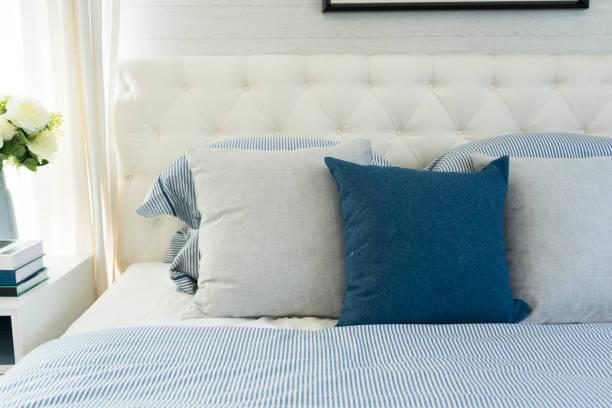 strand blauen kissen auf dem bett im schlafzimmer - cottage schlafzimmer stock-fotos und bilder