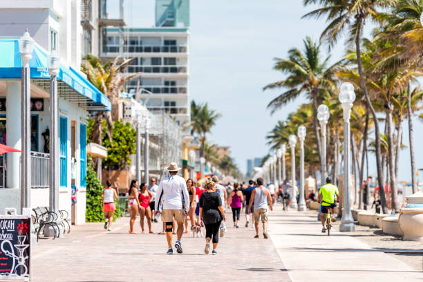 Beach boardwalk in Florida Miami Broward county with sunny day and people walking on promenade coast by cafe and restaurants exercising Hollywood, USA - May 6, 2018: Beach boardwalk in Florida Miami Broward county with sunny day and people walking on promenade coast by cafe and restaurants exercising boardwalk stock pictures, royalty-free photos & images