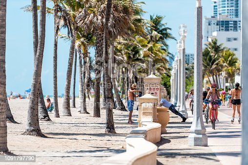 Hollywood, USA - May 6, 2018: Beach boardwalk in Florida Miami with sunny day and people walking on promenade coast man exercising push ups on fence