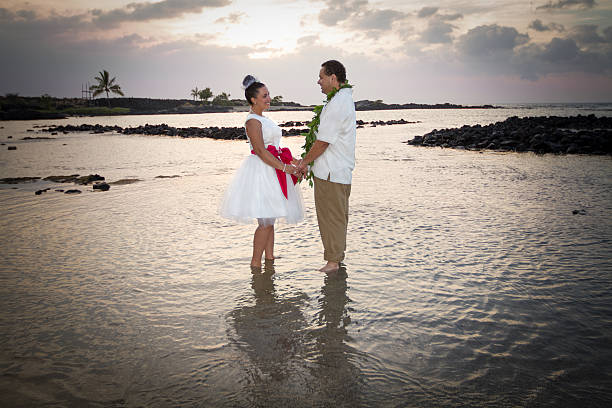 Beach Bride and Groom Newlywed couple standing in the warm, shallow watters of Hawaii. neicebird stock pictures, royalty-free photos & images