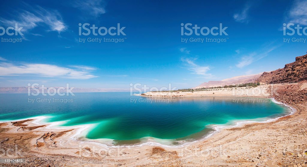 A beach by the Dead Sea with blue skies and turquoise water stock photo