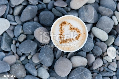 Cappuccino cup with heart on the beach
