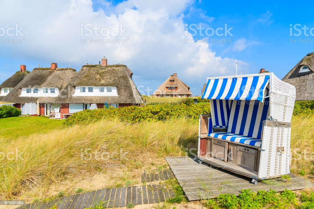 Beach chair on sand dune and typical cottages in List village, Sylt island, Germany stock photo