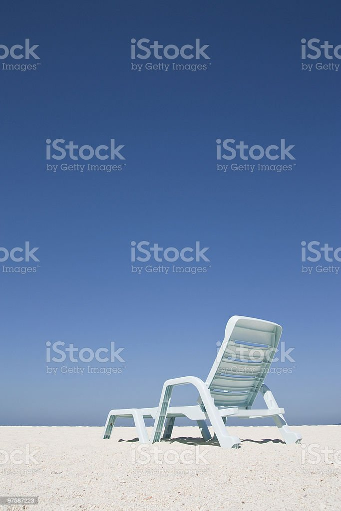 Beach chair on white sand and blue sky royalty-free stock photo