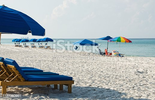 Empty beach chairs lined up along the Gulf of Mexico in Panama City Beach Florida. Tourists flock to this travel destination because of the white sand and emerald green water.