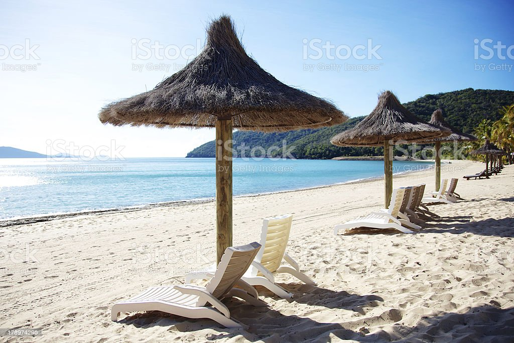 Beach chairs and grass umbrellas at resort royalty-free stock photo