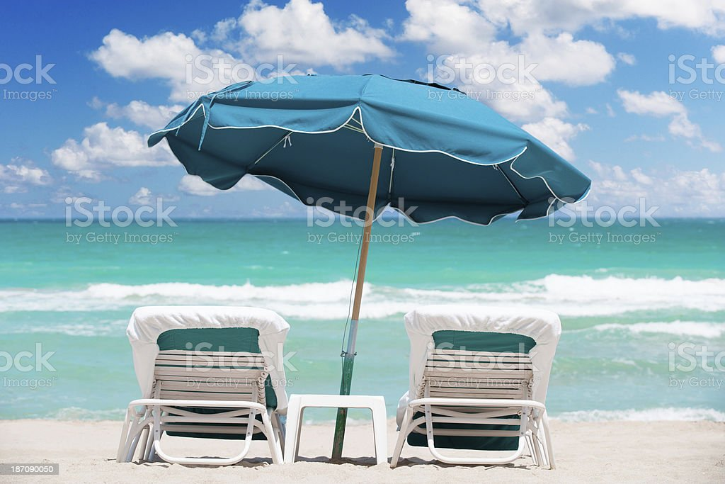 Beach chairs and umbrella in tropics royalty-free stock photo